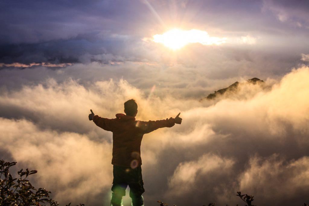 朝日に向かって喜びを表現している写真
